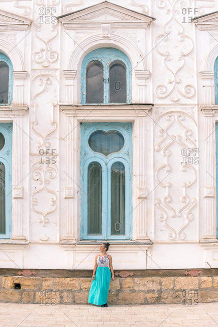 Lady in dress walking down steps outside shabby ornamental building on sunny day in Bukhara, Uzbekistan