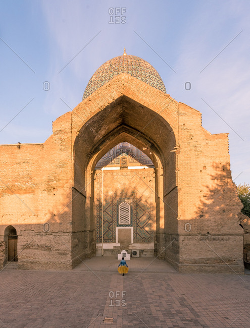 Back view of unrecognizable woman standing in doorway of shabby ornamental building in Samarkand, Uzbekistan