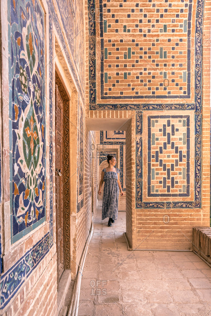 Woman admiring ornaments on walls of old building while visiting Samarkand, Uzbekistan