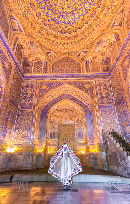 Back view of anonymous female in traditional gown standing in middle of illuminated ornamental building while visiting Registan in Samarkand, Uzbekistan