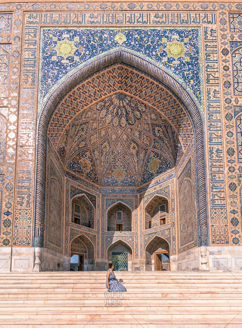 Side view of woman sitting outside arched ornamental building while visiting Registan in Samarkand, Uzbekistan