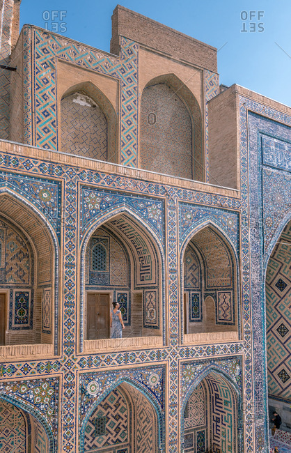 Female traveler walking on terrace of arched Islamic building with blue ornaments while visiting Registan in Samarkand, Uzbekistan