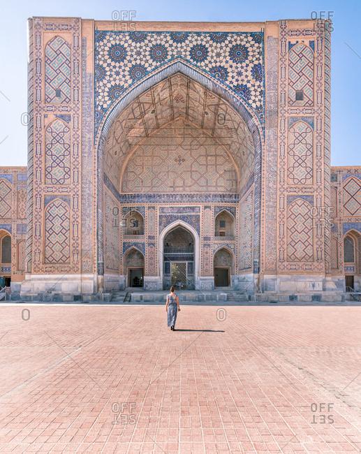 Back view of unrecognizable woman standing in doorway of shabby ornamental building Registan in Samarkand, Uzbekistan