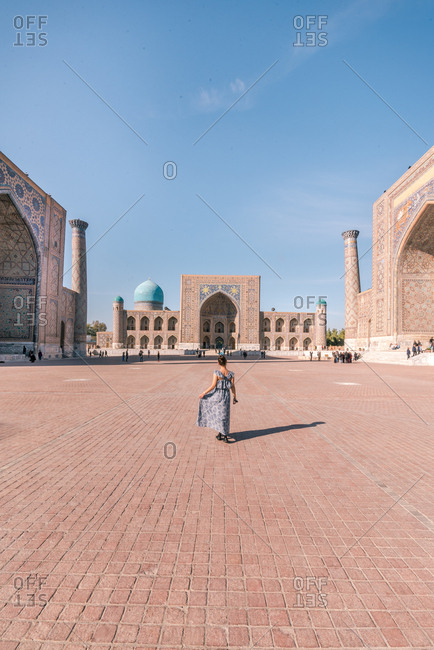 Back view of anonymous woman in dress walking on paved square near traditional Islamic buildings while visiting Registan in Samarkand, Uzbekistan