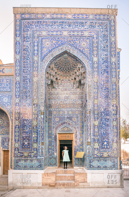 Woman standing in doorway of shabby ornamental building of Islamic Shah-i-Zinda necropolis in Samarkand, Uzbekistan