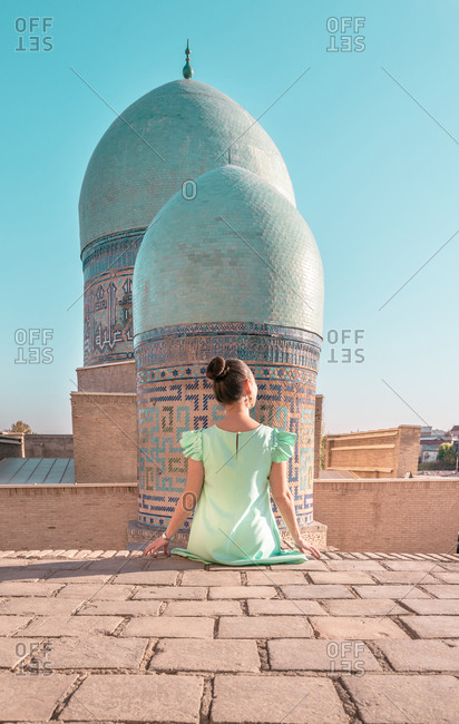 Back view of anonymous woman sitting on old building against shabby domes of Shah-i-Zinda on sunny day in Samarkand, Uzbekistan