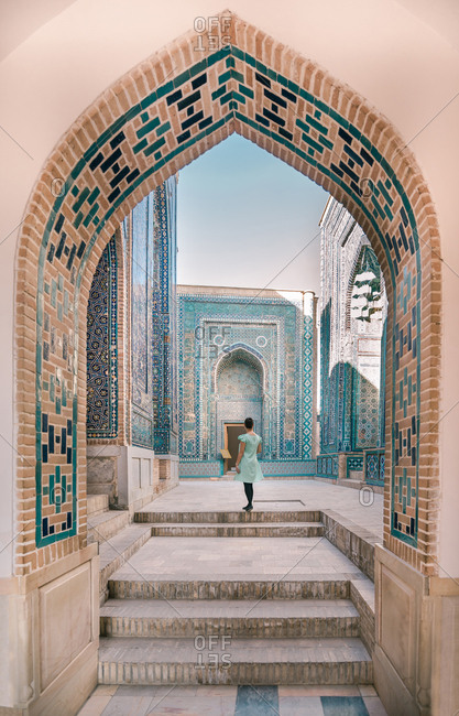 Back view of female traveler walking in arched passage of old building during trip in Uzbekistan