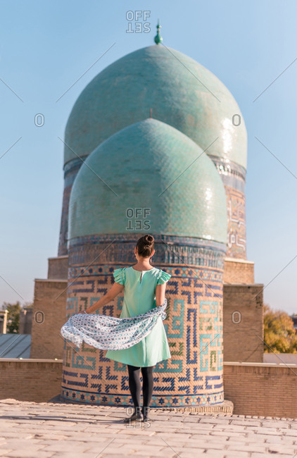 Back view of anonymous woman standing on old building against shabby domes of Shah-i-Zinda on sunny day in Samarkand, Uzbekistan