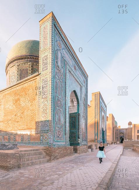 Female tourist walking on sidewalk near aged ornamental building of Shah-i-Zinda necropolis on sunny day in Samarkand, Uzbekistan