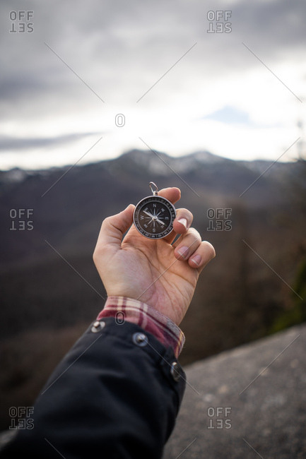 Crop man in jacket holding modern compass in outstretched hand while standing at rocky area