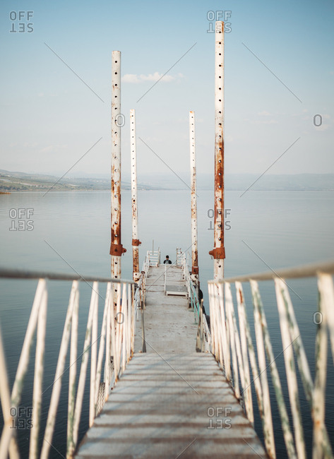 Narrow pier with weathered railings and distant traveler located near tranquil sea water against cloudless sky