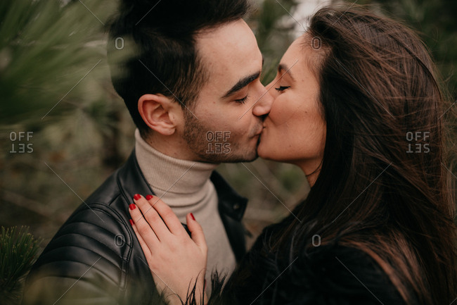 Side view of couple in love with closed eyes smiling while embracing and kissing each other along coniferous trees during daytime in windy overcast weather