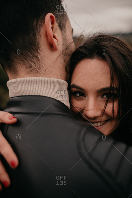 Young woman in love embracing unrecognizable boyfriend and smiling while looking at camera during daytime