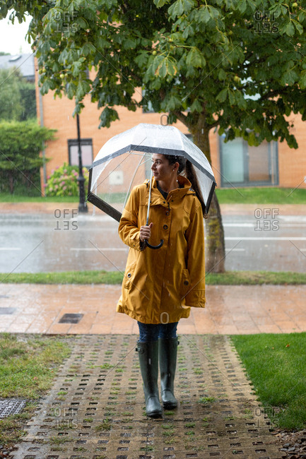 Young woman in yellow raincoat and dark rubber boots with transparent umbrella standing under rain in street and looking away