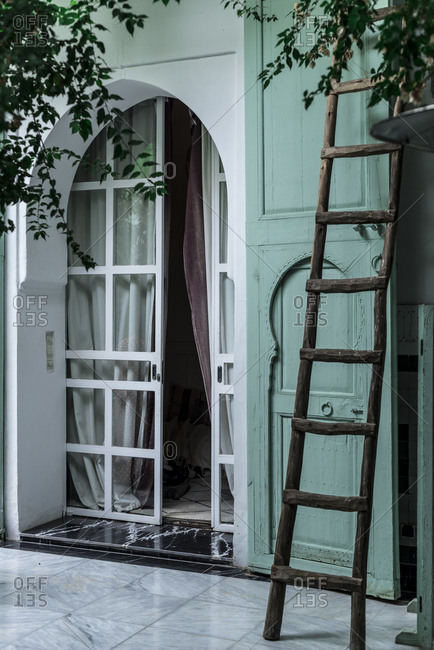 Old wooden ladder located near entrance of traditional Arabic building with green walls on street of Marrakesh, Morocco
