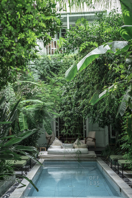 October 22, 2018: Swimming pool and couch located amidst green exotic plants outside hotel building in Marrakesh, Morocco
