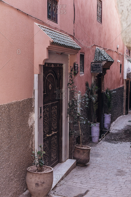 October 23, 2018: Pots with plants placed outside doors of shabby building on street of Marrakesh, Morocco