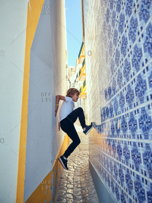 Playful boy scrambling on decorative wall on narrow alley on street in Portugal