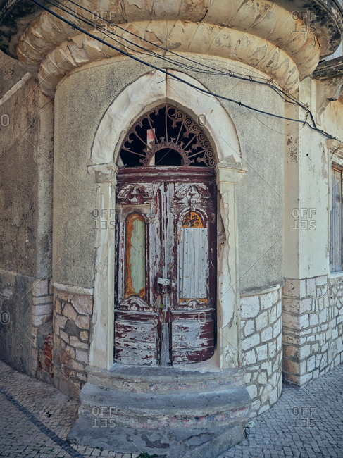September 2, 2019: Abandoned house with shabby arched door and concrete doorsteps on street of old city in Portugal