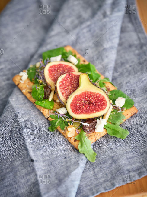 Homemade delicious colorful open sandwich with slices of fig and pieces of cheese on crisp rye bread among aromatic green leaves of rocket salad