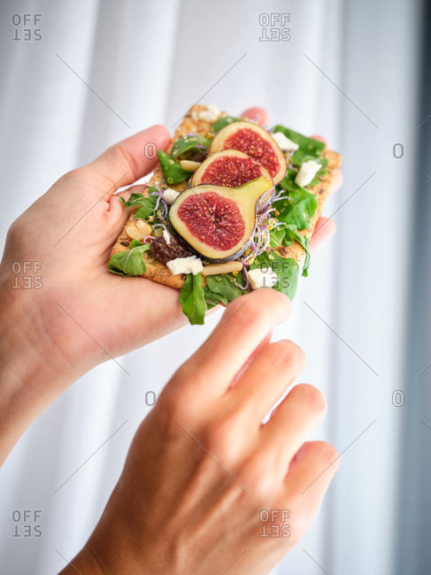 Crop person holding homemade colorful open sandwich with slices of fig and pieces of cheese on crisp rye bread with aromatic green leaves of rocket salad against white wall