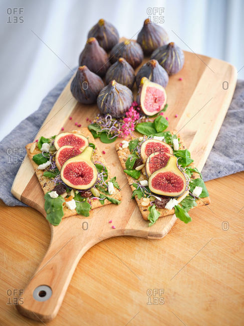 Homemade tasty colorful open sandwiches with slices of fig and pieces of cheese on crisp rye bread among aromatic green leaves of rocket salad and pink flowers