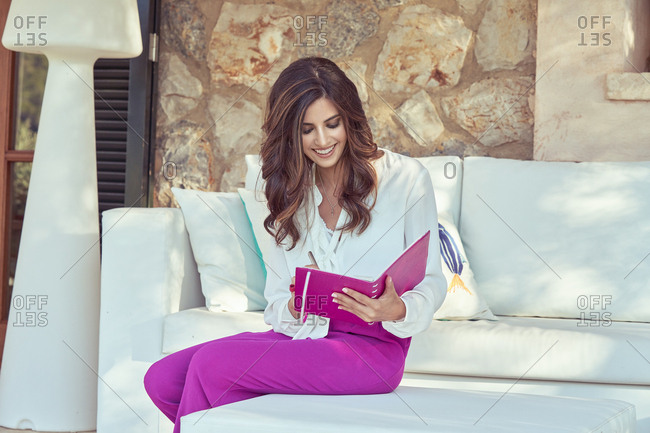 Long haired curly beautiful woman in pink pants sitting on coach and looking at camera while writing in notebook with pink cover