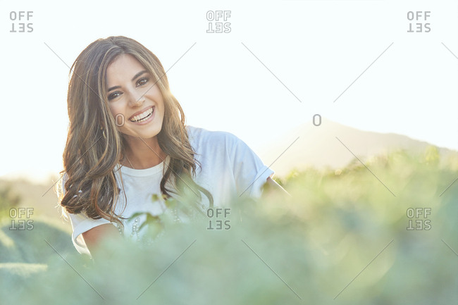 Graceful stylish beautiful young woman in green garden looking at camera with smiling