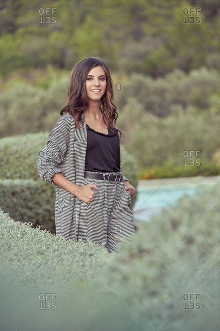 Stylish woman in elegant gray suit standing with hands in pocket in garden looking at camera smiling
