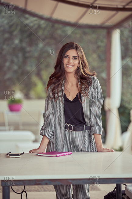 Stylish woman in gray elegant suit leaning on table with notebook in street cafe looking at camera