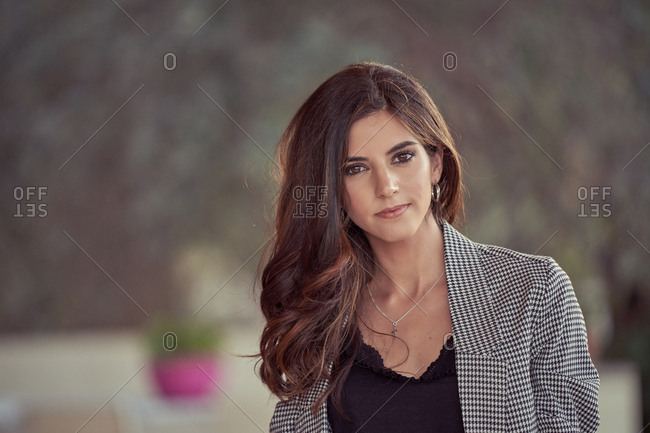 Stylish beautiful young woman in gray elegant suit looking at camera