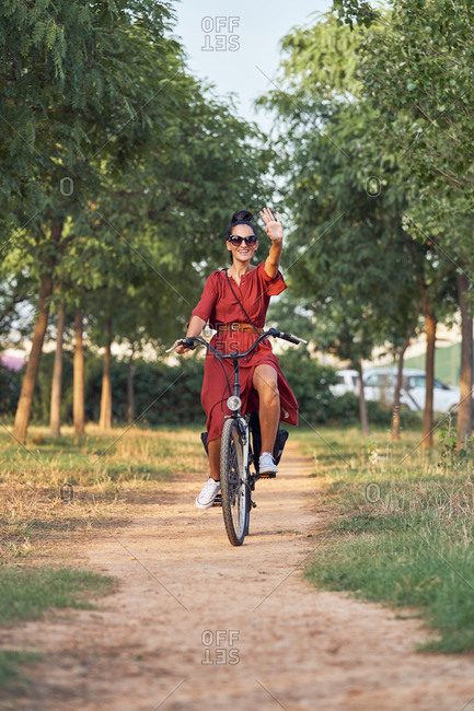 Happy smiling lady in red dress riding a bike and along path on sunny day in park