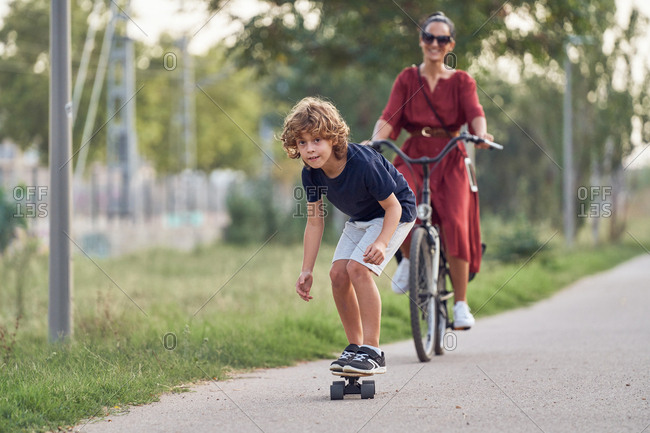 Full body focused boy riding skateboard in front of cheerful woman on bicycle along asphalt path while spending time in park together