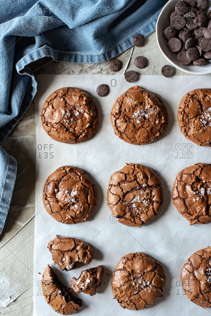 From above composition of delicious chocolate brownie cookies on white parchment and blue towel