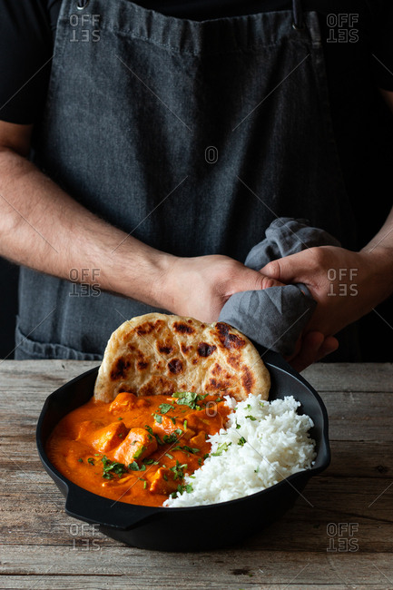 Crop person in apron standing by wooden table with skillet full of delicious butter chicken and rice