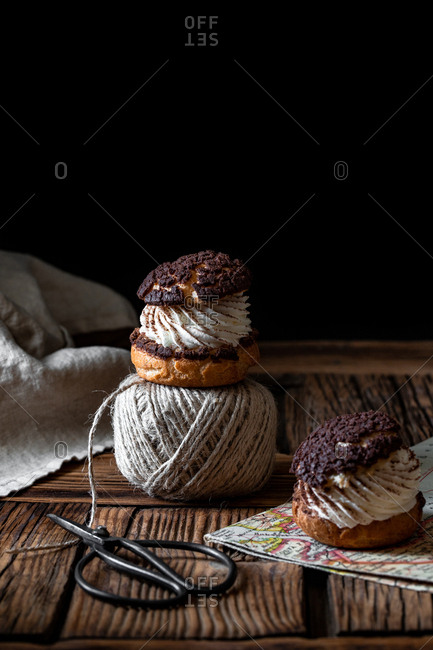 Homemade choux pastries with cream and chocolate scissors and ball of yarn arranged on texture wooden surface against black background