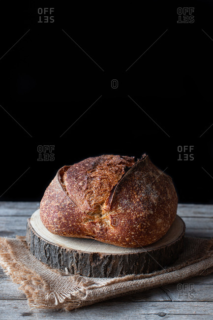 Loaf of fresh country sourdough bread placed on piece of wood on shabby table against black background