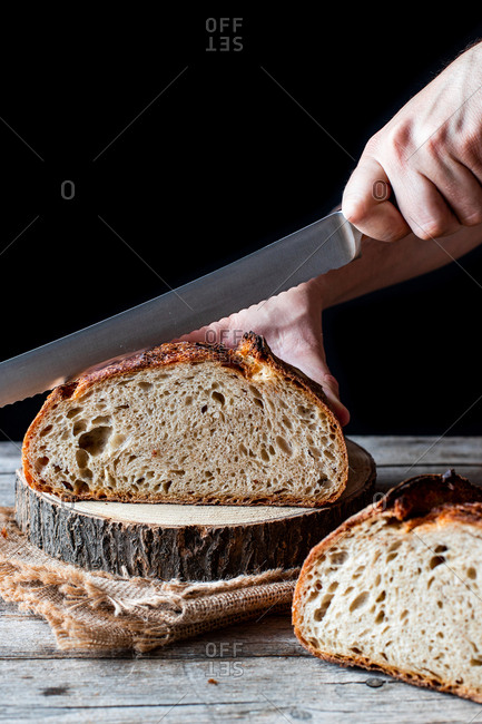 Unrecognizable person using knife to cut loaf of fresh sourdough bread on piece of wood against black background