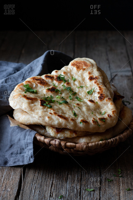 Plate with delicious naan bread and cloth napkin placed on weathered lumber table