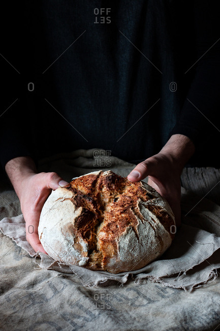 Unrecognizable person putting loaf of payes bread on linen cloth on table against black background