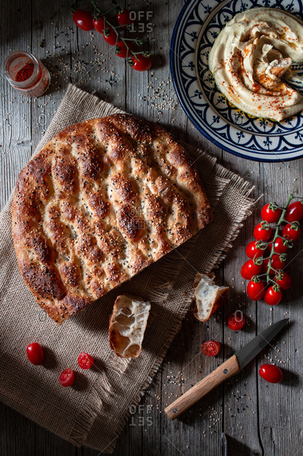 From above loaf of Ramazan pidesi placed near fresh tomatoes and spices on lumber tabletop