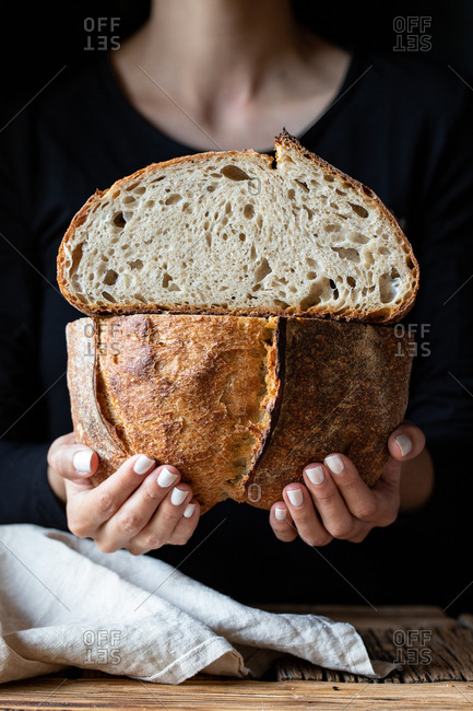 Unrecognizable person showing fresh halved bread with seeds against wooden wall
