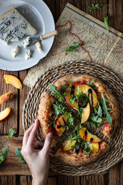 From above unrecognizable person taking piece of yummy summer pizza with peach and arugula near map and cheese on wooden table