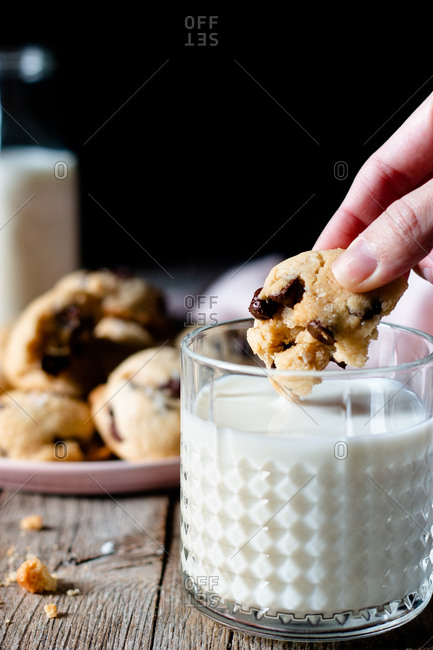 Unrecognizable female dipping piece of yummy vegan cookie with chocolate chips into glass of fresh milk on wooden table against black background