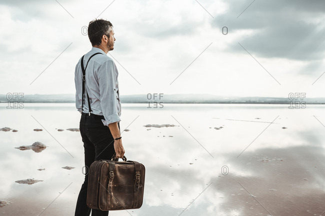 Side view of man in white shirt and suspenders carrying shabby briefcase while standing barefoot looking away on gloomy beach in USA