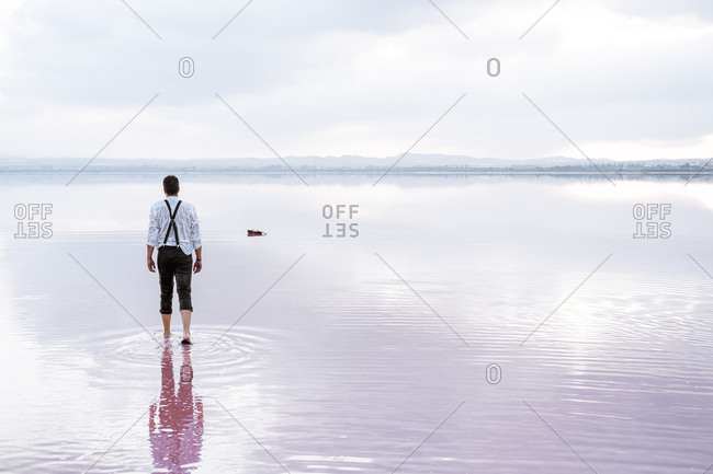 Back view serious man in white shirt and rolled up pants coming walking towards a guitar in gradient sea