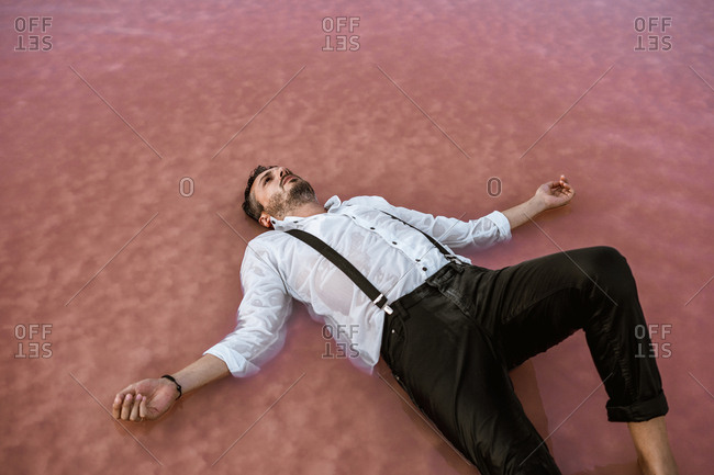 From above classy man in white shirt and suspenders lying on back and floating with outstretched hands in sea at sandbank