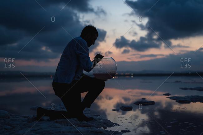 Side view of man kneeling and filling empty aquarium wit ocean water at seaside in twilight