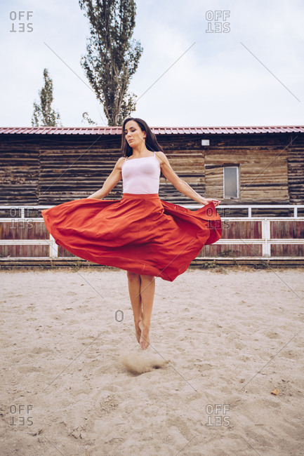 Artistic woman in red skirt jumping at sandy enclosure by farm barn in daylight