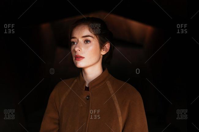 Pensive woman in coat looking away